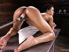 Ebony babe Kira Noir is getting both holes toyed by a fucking machine